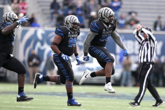 Memphis' Bryce Huff, right, celebrates his tackle against Houston Cougars as the Tigers win the AAC West title 52-31 at the Liberty Bowl on Friday, Nov. 23, 2018.