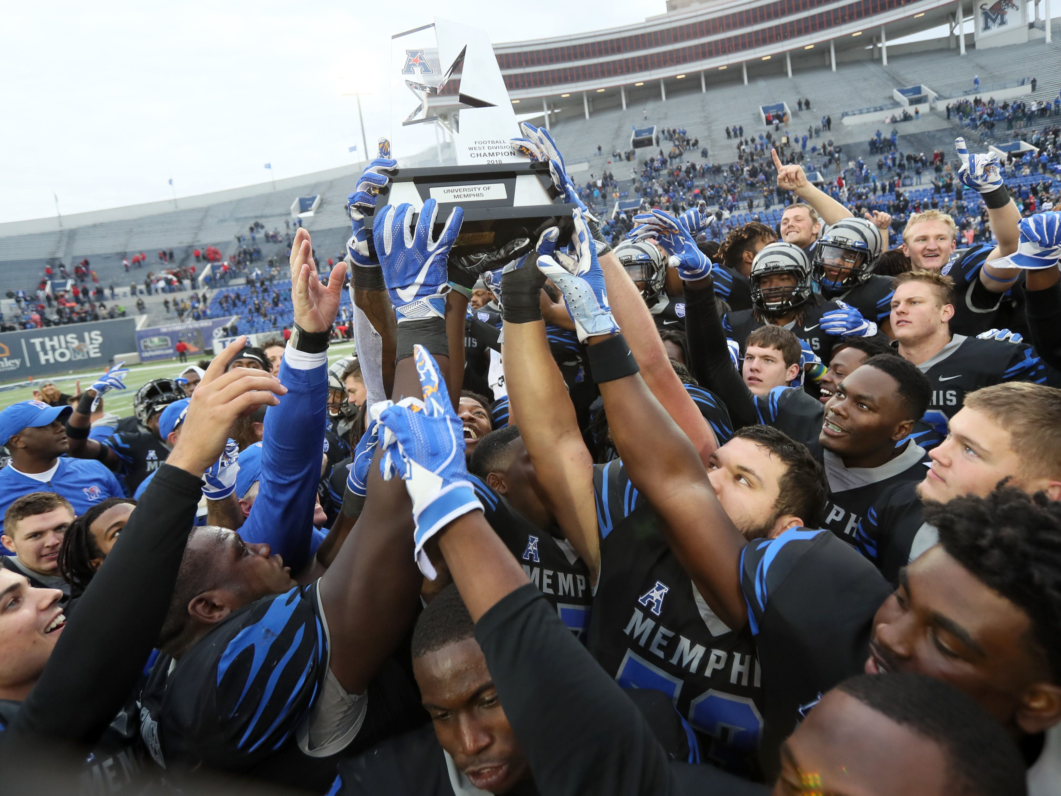Memphis players hold their trophy after winning the AAC West title against Houston 52-31 at the Liberty Bowl on Friday, Nov. 23, 2018.
