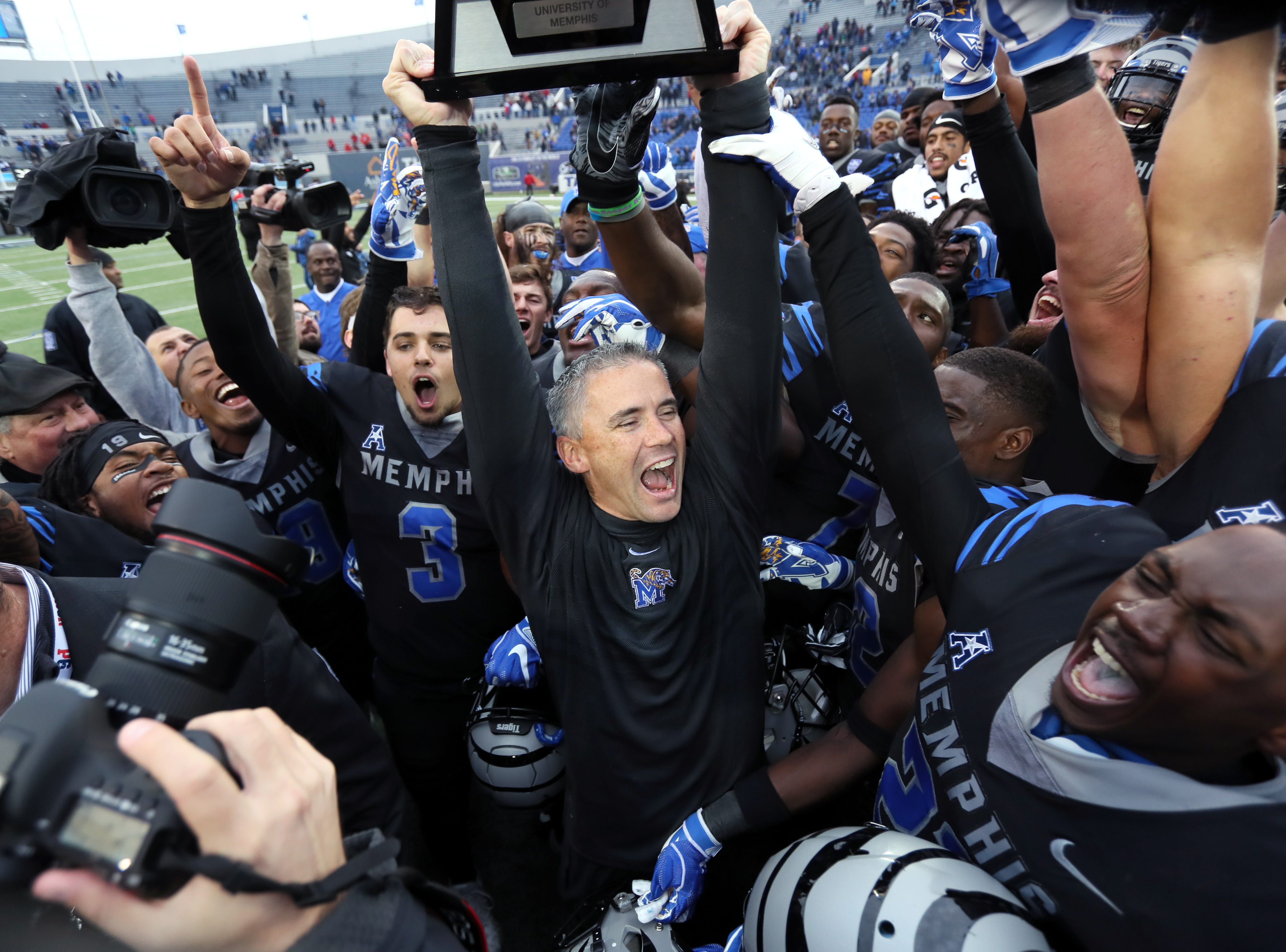 Memphis Head Coach Mike Norvell celebrates with his players as they defeat the Houston Cougars to win the AAC West title 52-31 at the Liberty Bowl on Friday, Nov. 23, 2018.