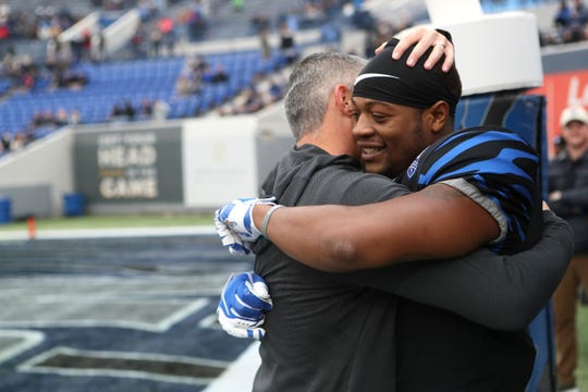 Memphis Tigers Head Coach Mike Norvell hugs senior Sam Craft before their game against the Houston Cougars at the Liberty Bowl on Friday, Nov. 23, 2018.