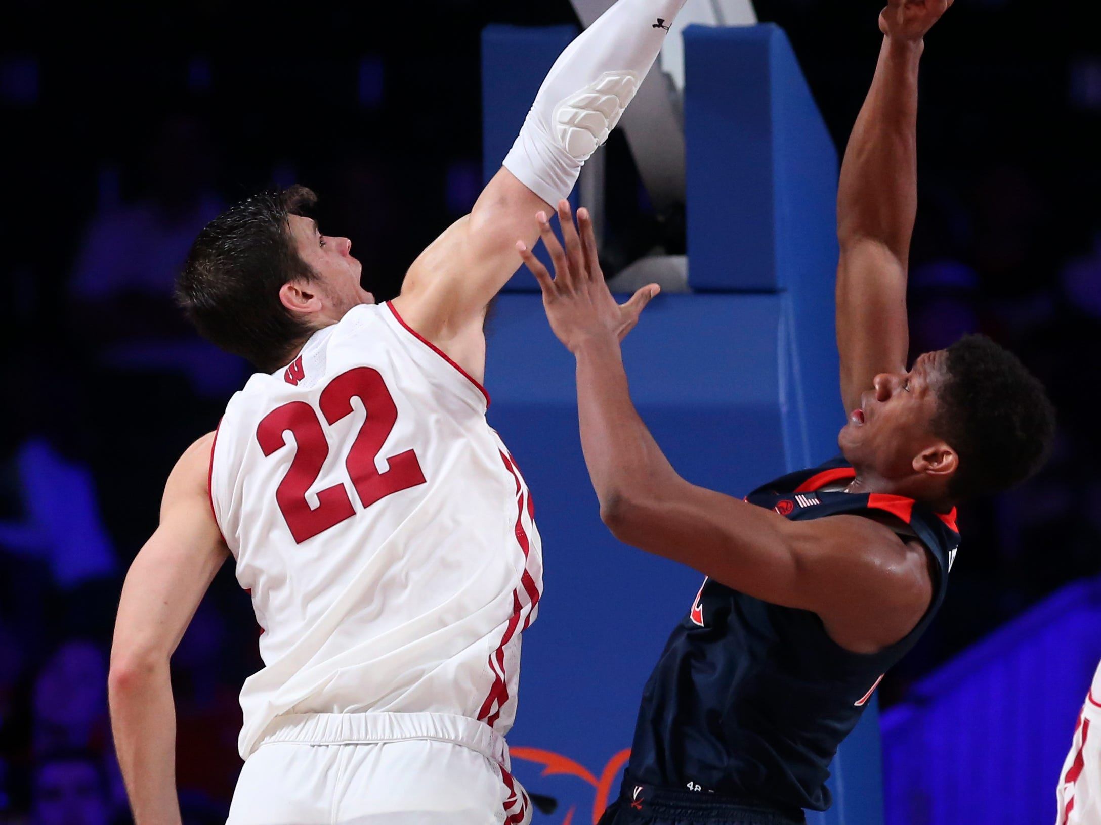 Badgers forward Ethan Happ defends the shot of Virginia Cavaliers guard De'Andre Hunter.