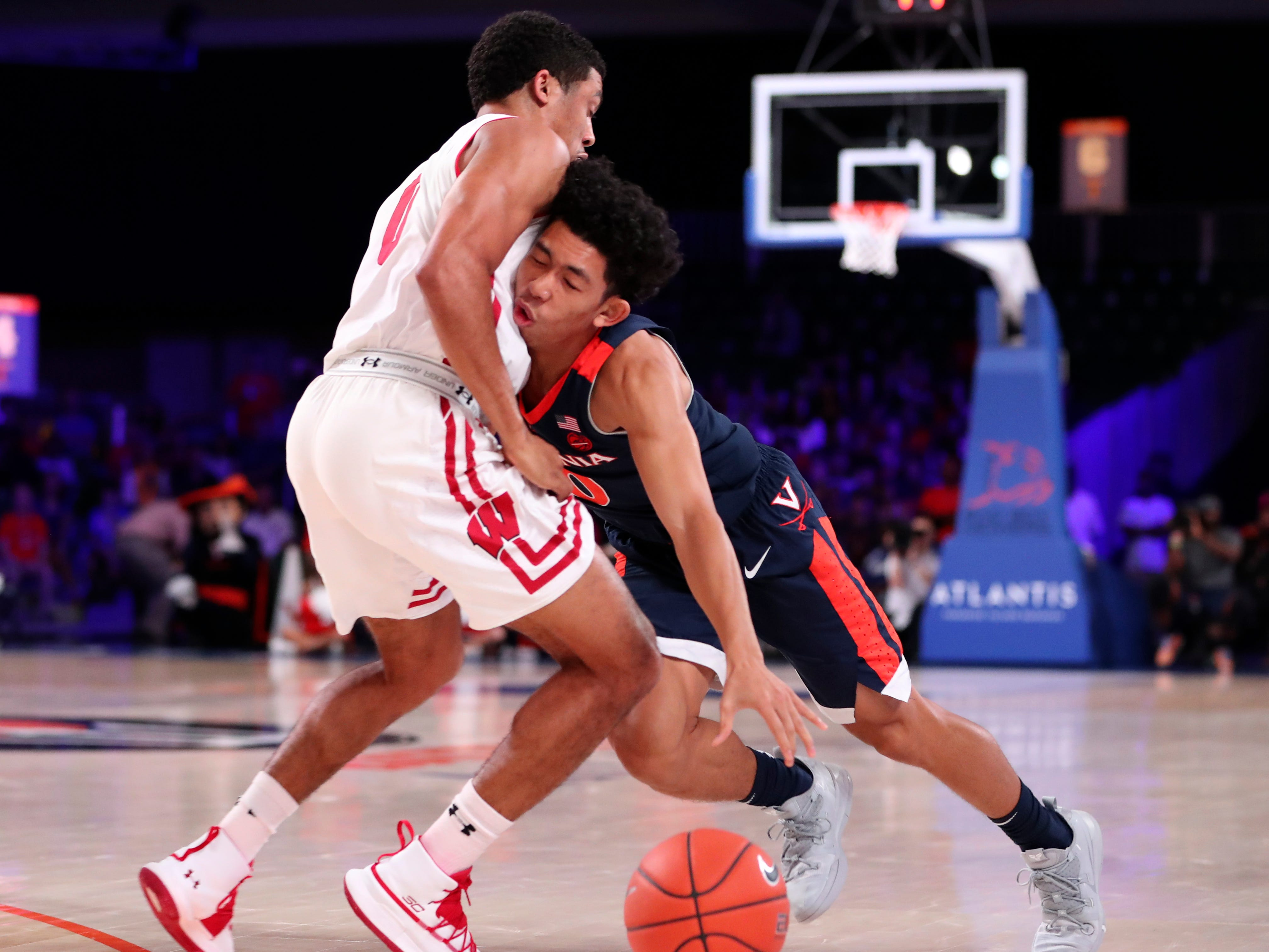 Virginia Cavaliers guard Kihei Clark runs into Badgers guard D'Mitrik Trice.