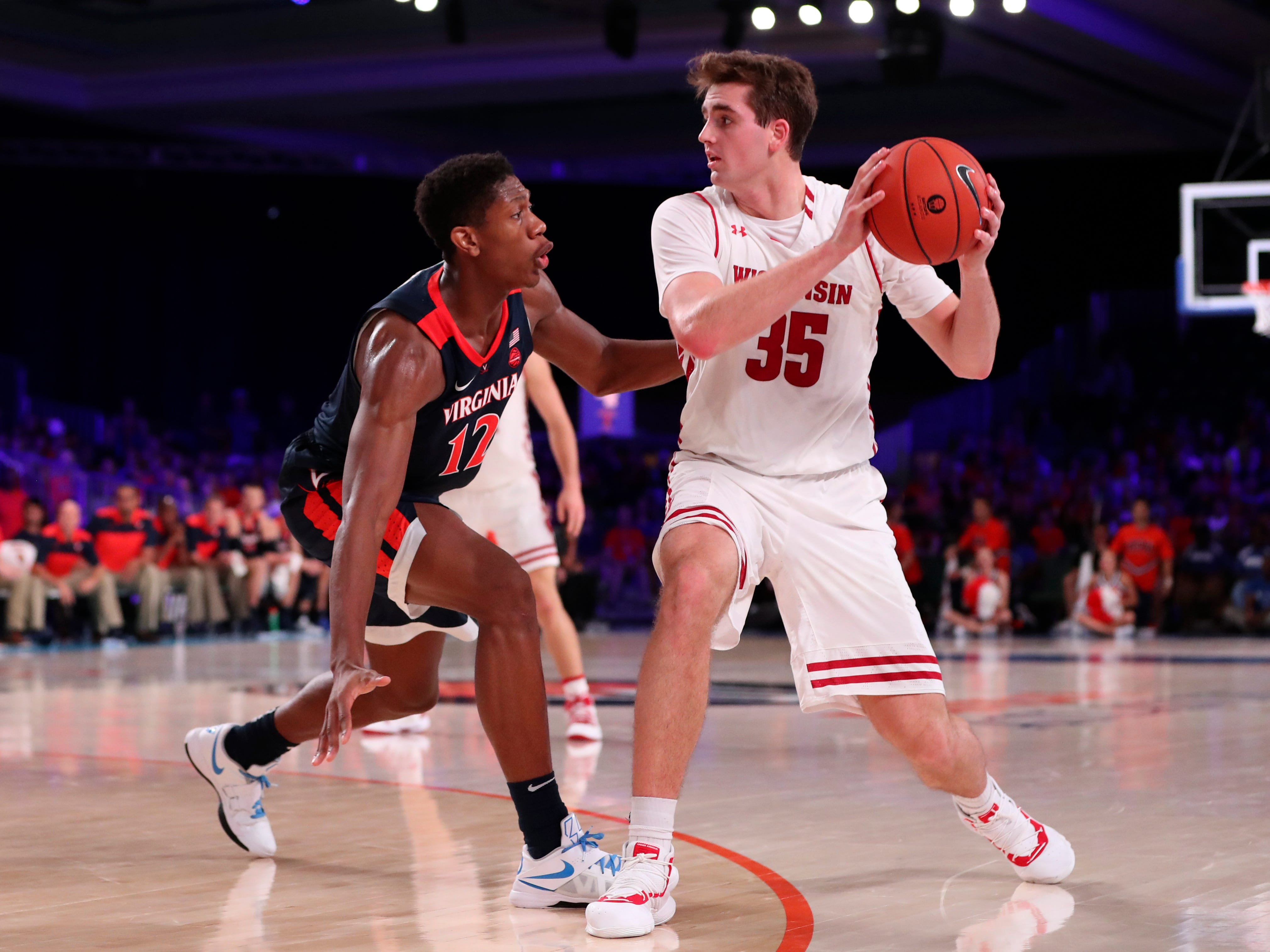 Badgers forward Nate Reuvers looks to pass over Virginia  guard De'Andre Hunter.