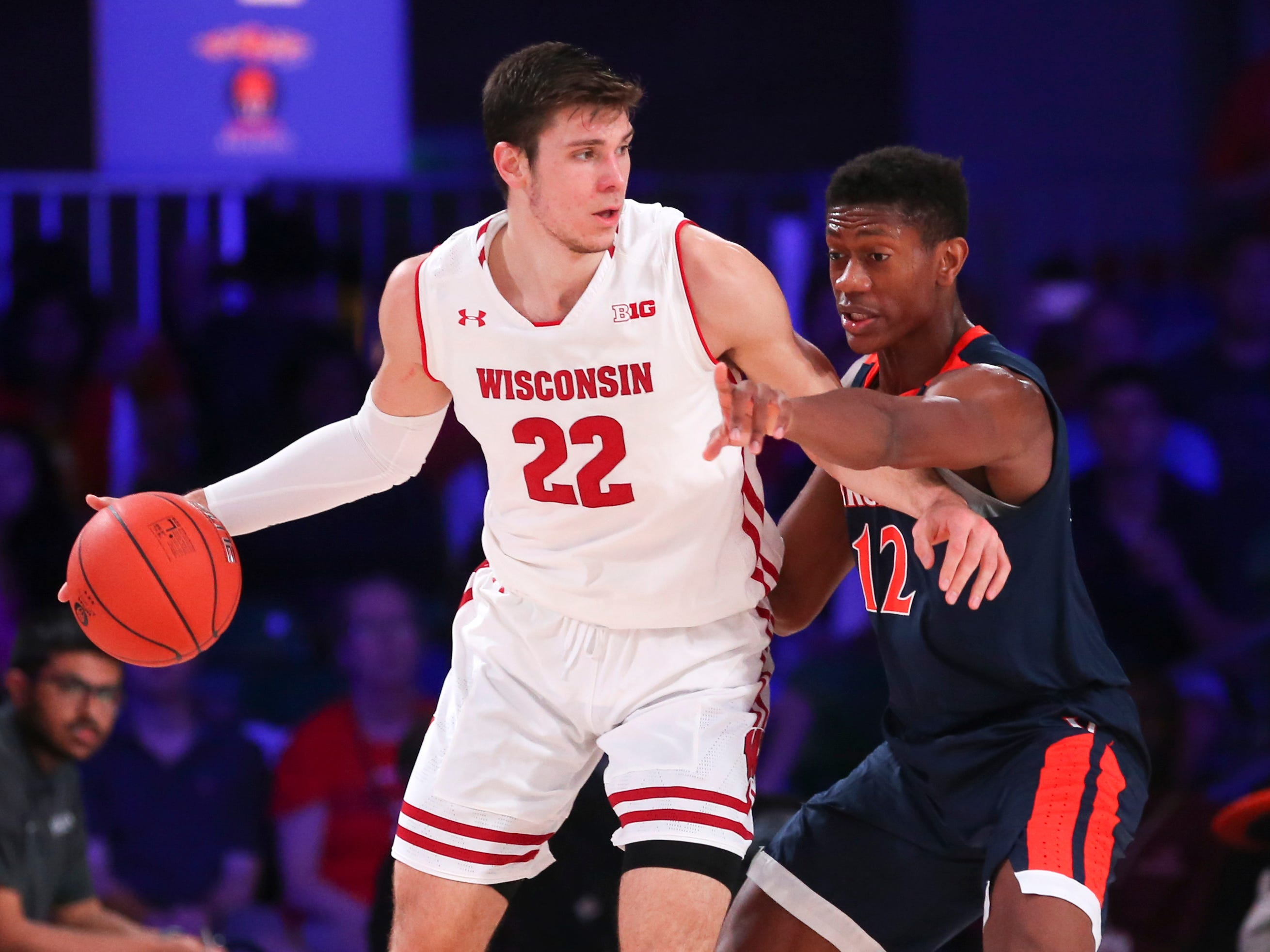 Wisconsin Badgers forward Ethan Happ is guarded by Virginia's De'Andre Hunter.