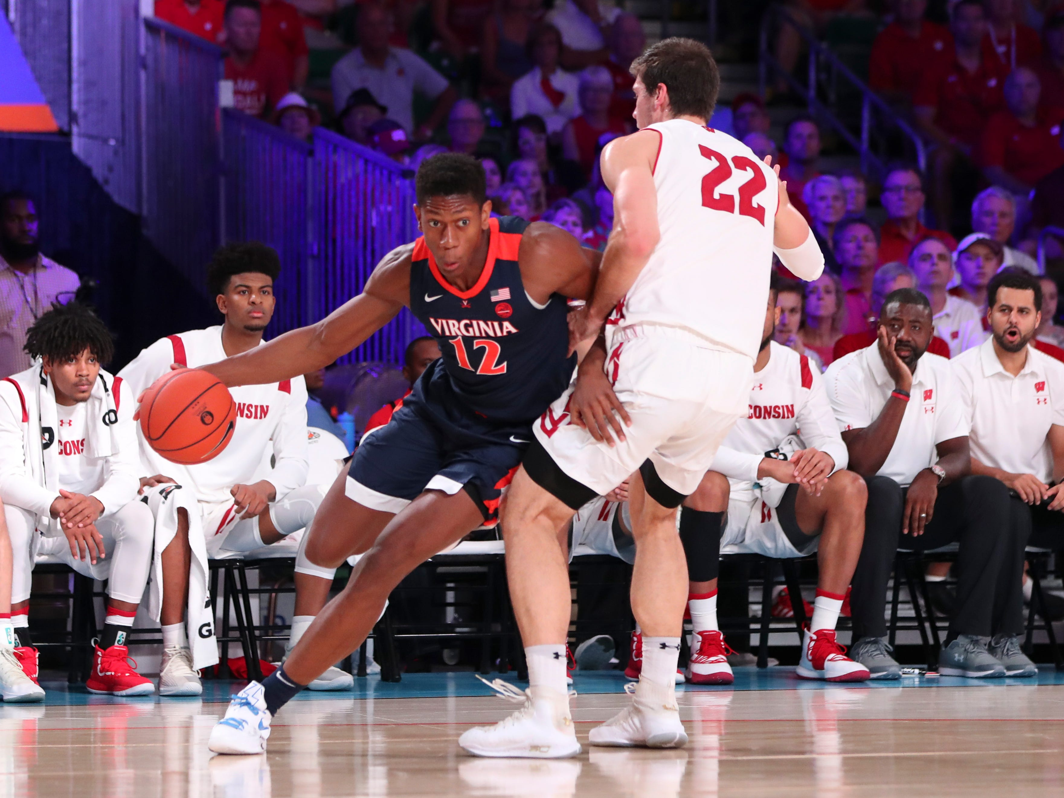 Virginia Cavaliers guard De'Andre Hunter drives to the basket past Badgers forward Ethan Happ.