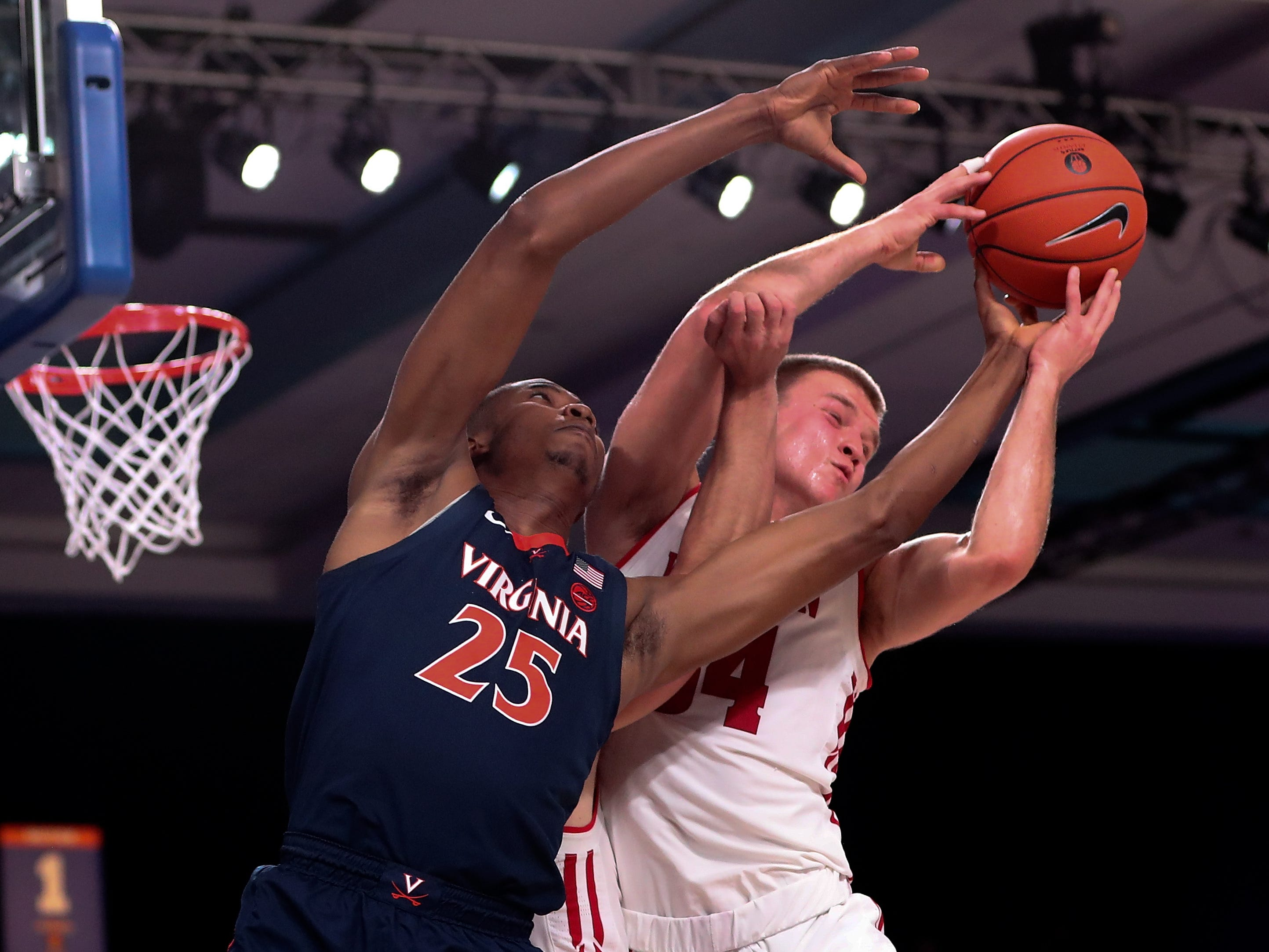 Badgers guard Brad Davison and Virginia Cavaliers forward Mamadi Diakite battle for a loose ball.