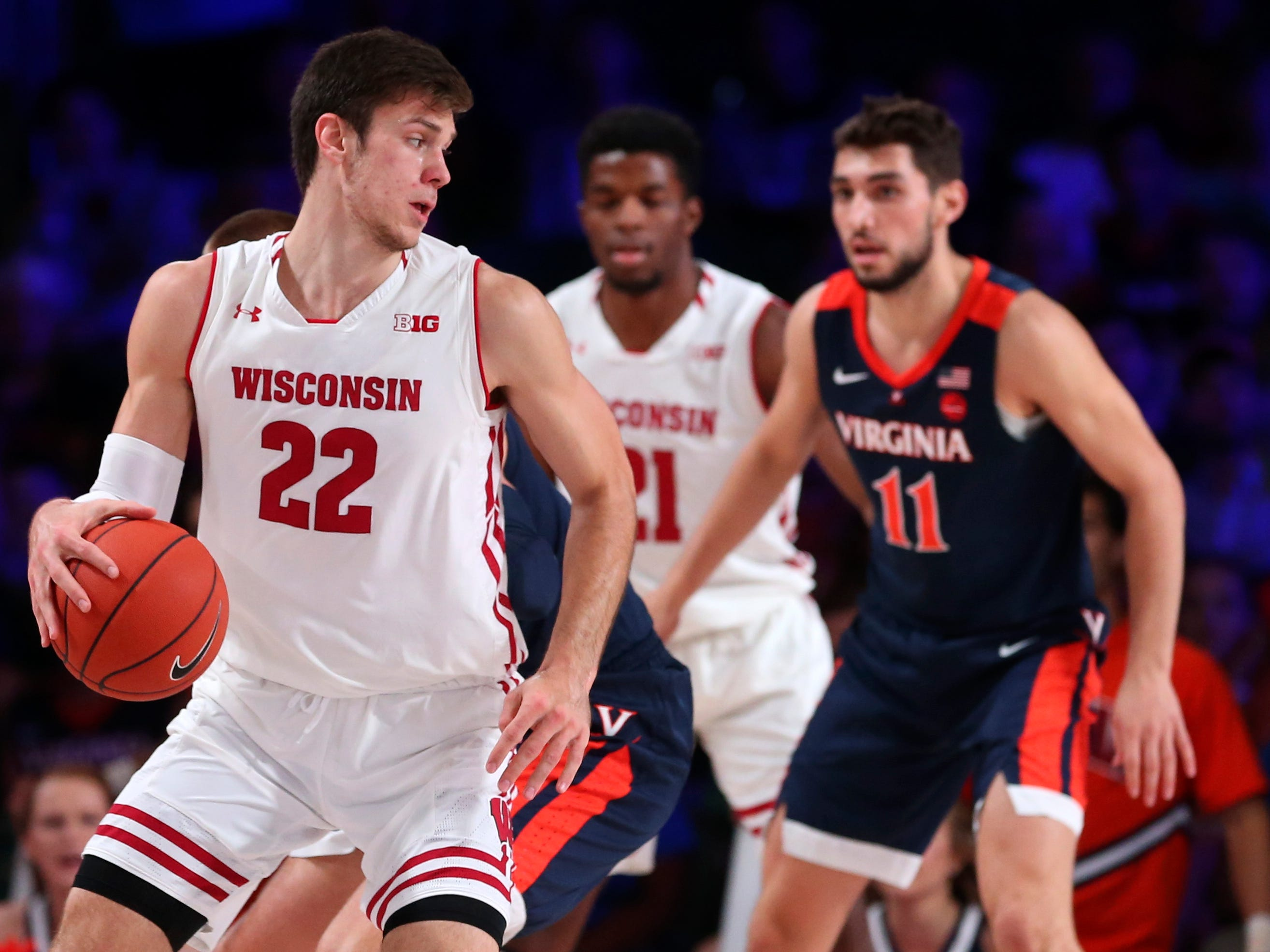 Badgers forward Ethan Happ tries to get past Virginia's Ty Jerome.