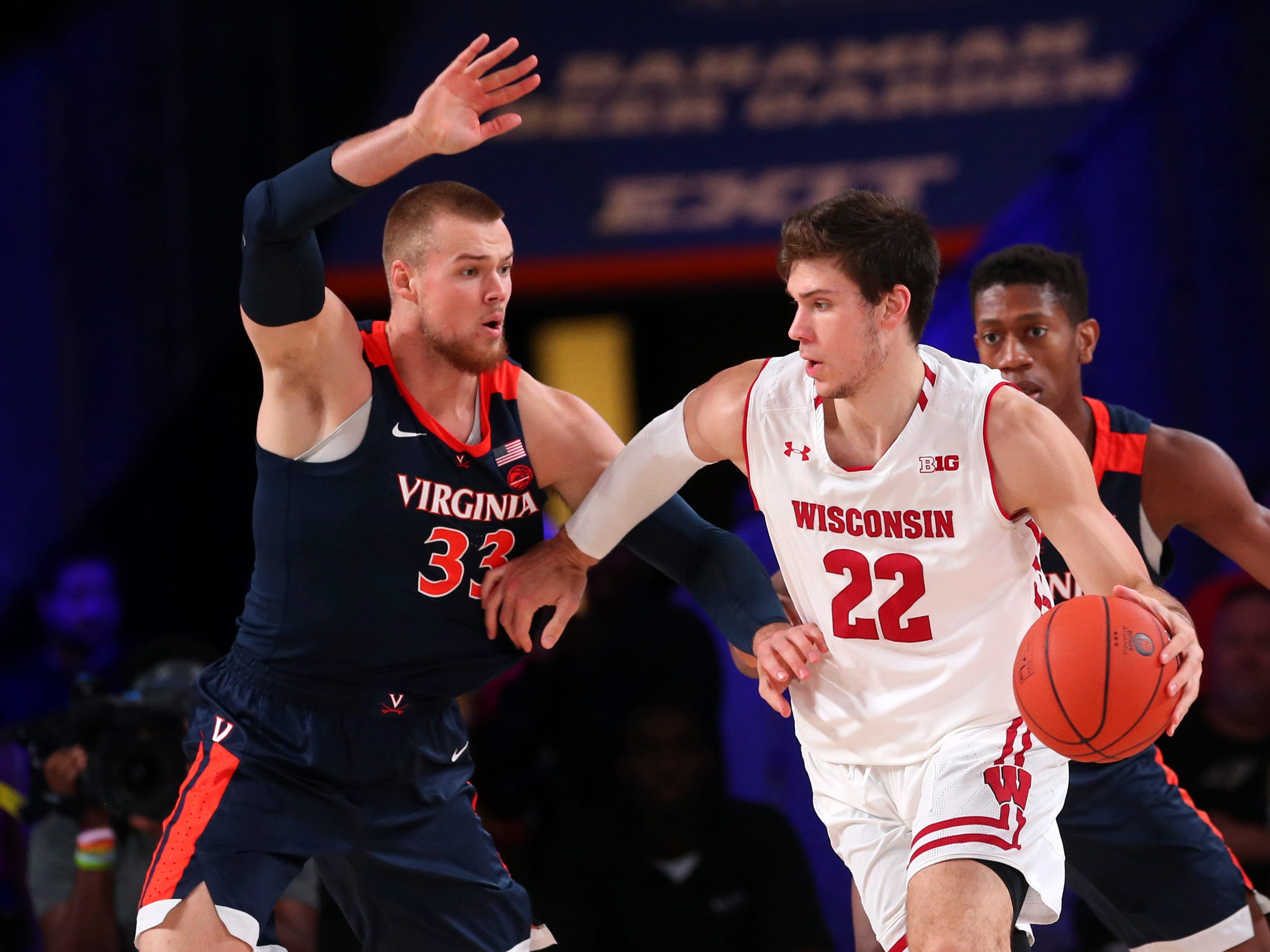 Badgers forward Ethan Happ is defended by Virginia's  Jack Salt.