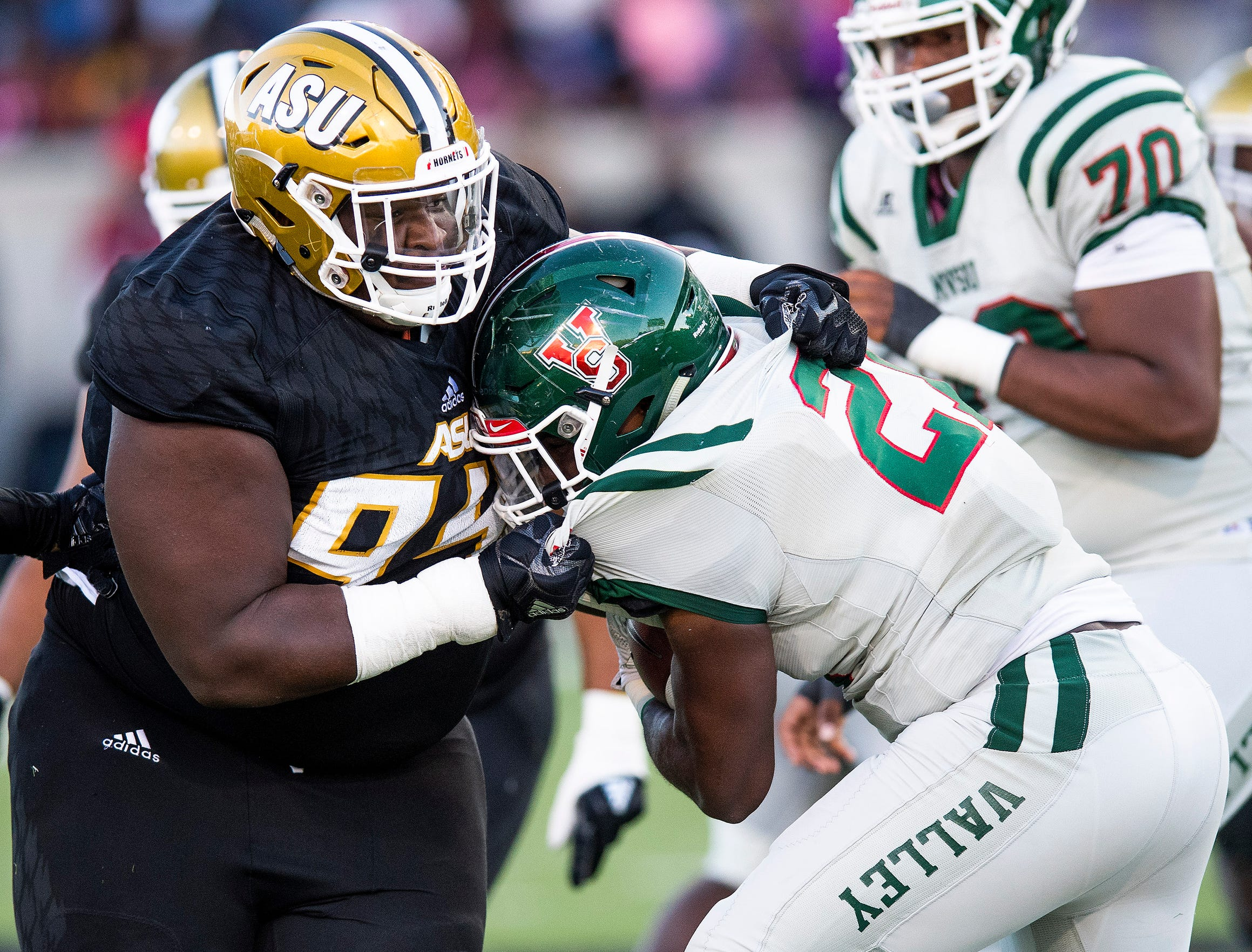 Mississippi Valley State running back Henry Isaiah Robinson (21) is stopped by Alabama State University defensive lineman Christian Clark (94) in the Turkey Day Classic at Hornet Stadium on the ASU campus in Montgomery, Ala., on Thanksgiving Day, Thursday November 22, 2018.