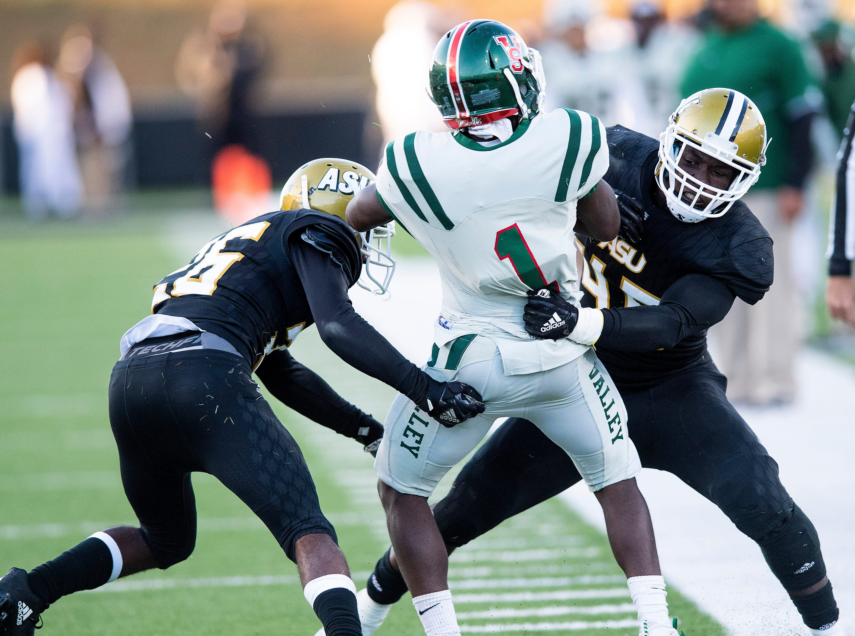 Alabama State University defensive back Kimar Martin (26)  and  linebacker Darron Johnson (46)  take Mississippi Valley State wide receiver Booker Chambers (1)  out of bounds in the Turkey Day Classic at Hornet Stadium on the ASU campus in Montgomery, Ala., on Thanksgiving Day, Thursday November 22, 2018.