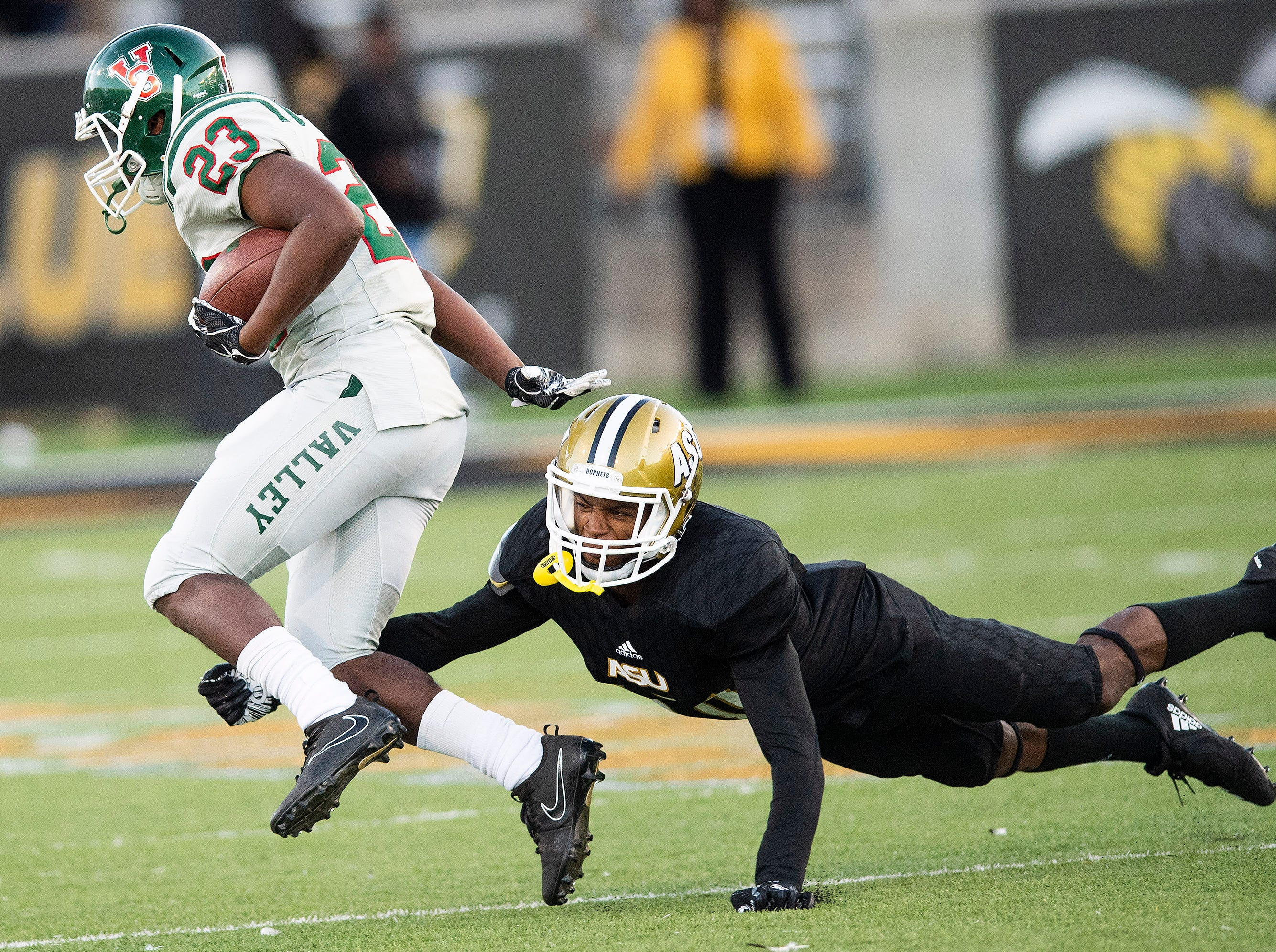 Alabama State University defensive back Keenan Isaac (10)  tries to trip up Mississippi Valley State running back John Derrick Smith (23) the Turkey Day Classic at Hornet Stadium on the ASU campus in Montgomery, Ala., on Thanksgiving Day, Thursday November 22, 2018.