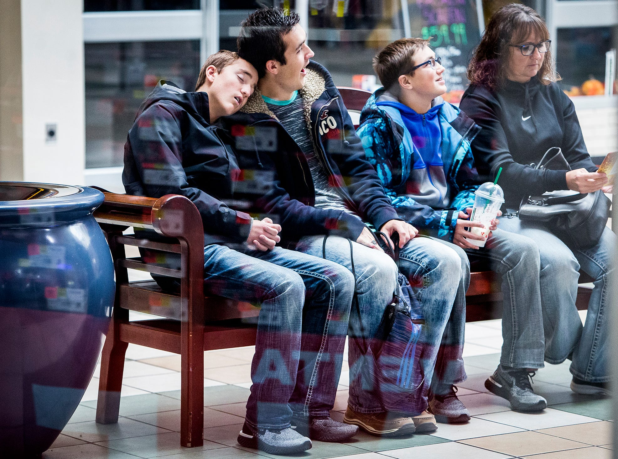 A group of shoppers takes a break at the Muncie Fall on Black Friday.