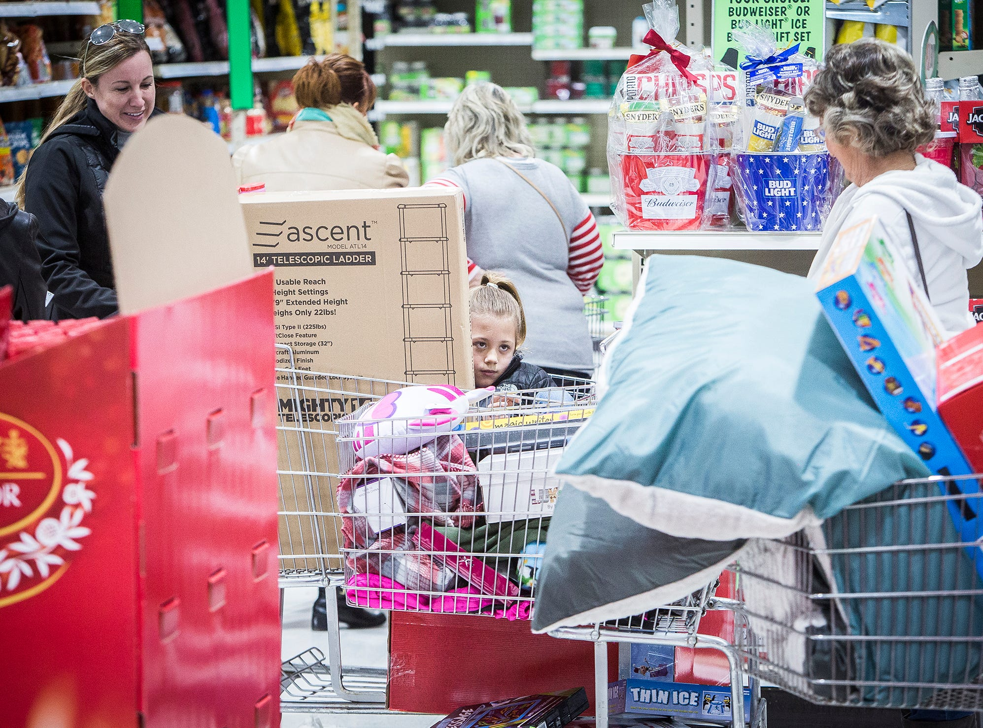 A child rides in a cart at Menards on Black Friday.