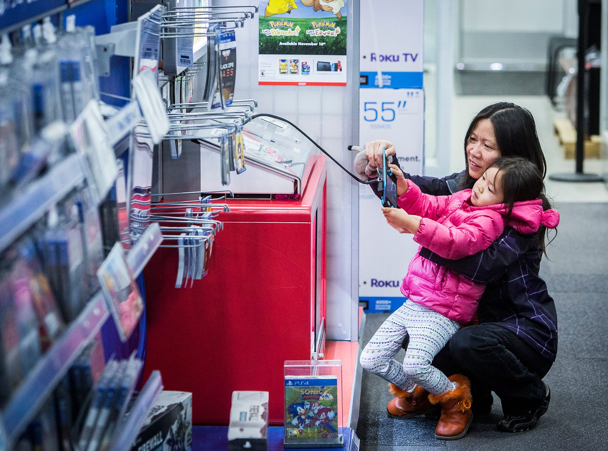 Customers at Best Buy play a video game during Black Friday.