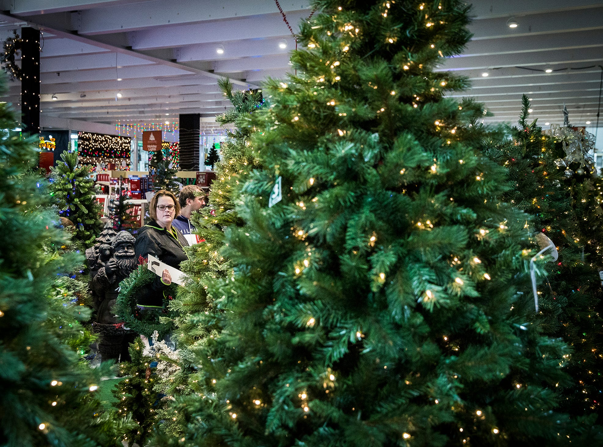 Shoppers check out Christmas trees on at Menards on Black Friday.