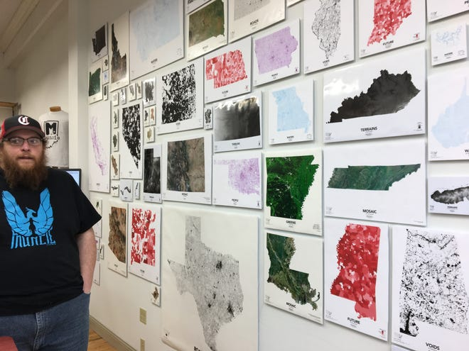 "Andy Shears stands beside one of his biggest projects, ""The United States of Data."" All 50 states, plus territories and national parks, are hung up and mapped according to different geographic characteristics such as population density and water features."