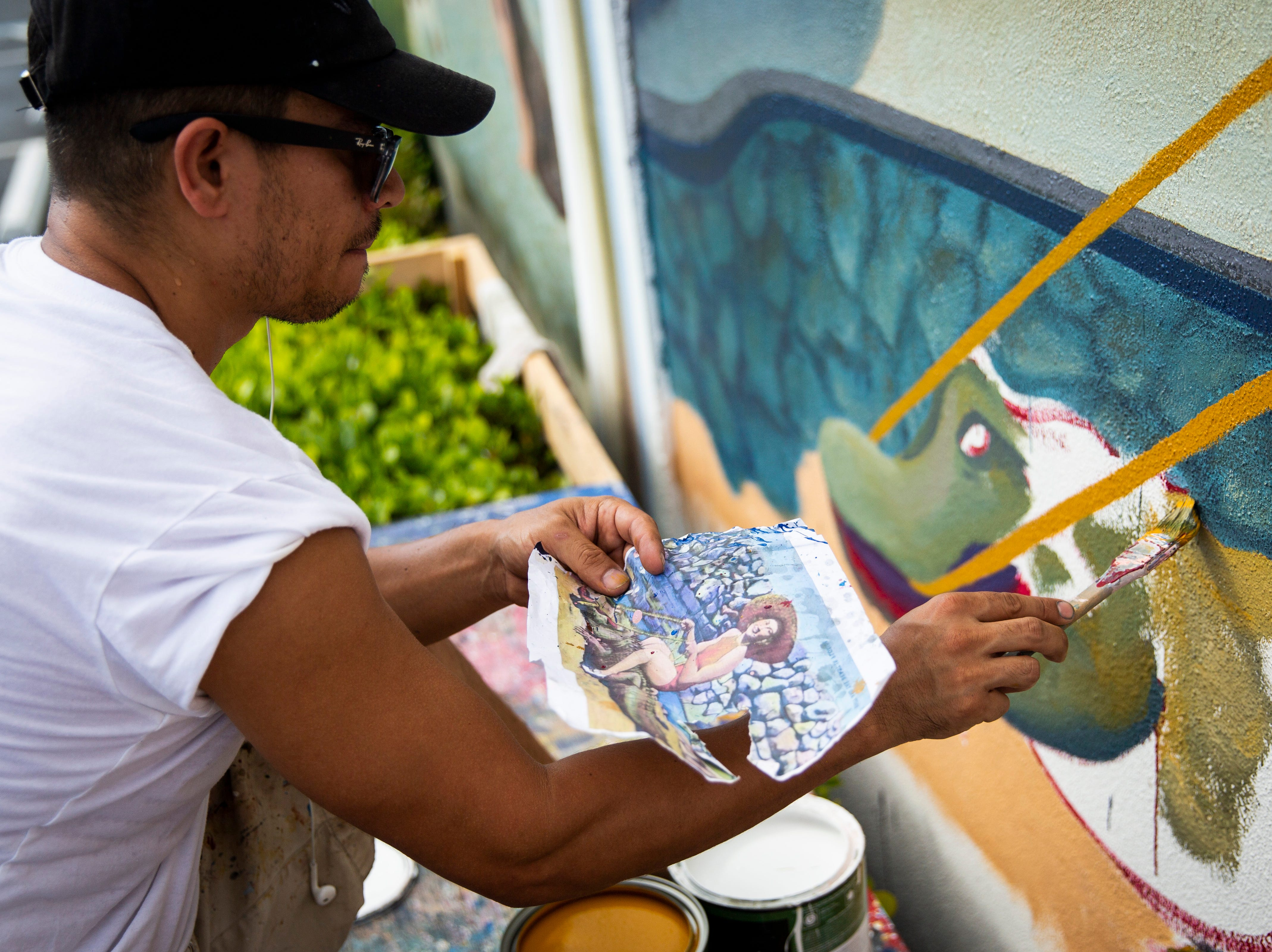 Naples artist Juan Diaz uses a printout of a vintage postcard as a reference while working on a mural on Friday, November 23, 2018, at the corner of U.S. 41 South and First Avenue South in Naples.
