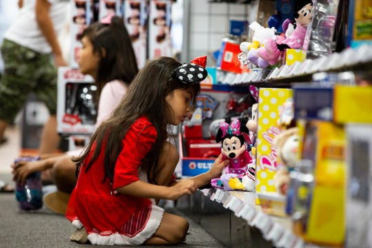 Six-year-old Sara Cerna spends some time playing with Disney toys while her parents shop for electronics at the Best Buy on Naples Boulevard Friday, Nov. 23, 2018, for their annual Black Friday sale.