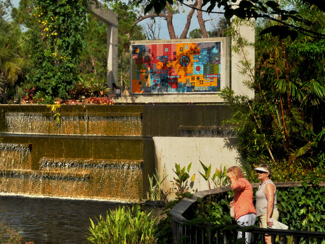 Visitors to the Naples Botanical Gardens are treated to a myriad of tropical plants. In the background is a piece of art  designed by Miami-based, award winning landscape architect Raymond Jungles.