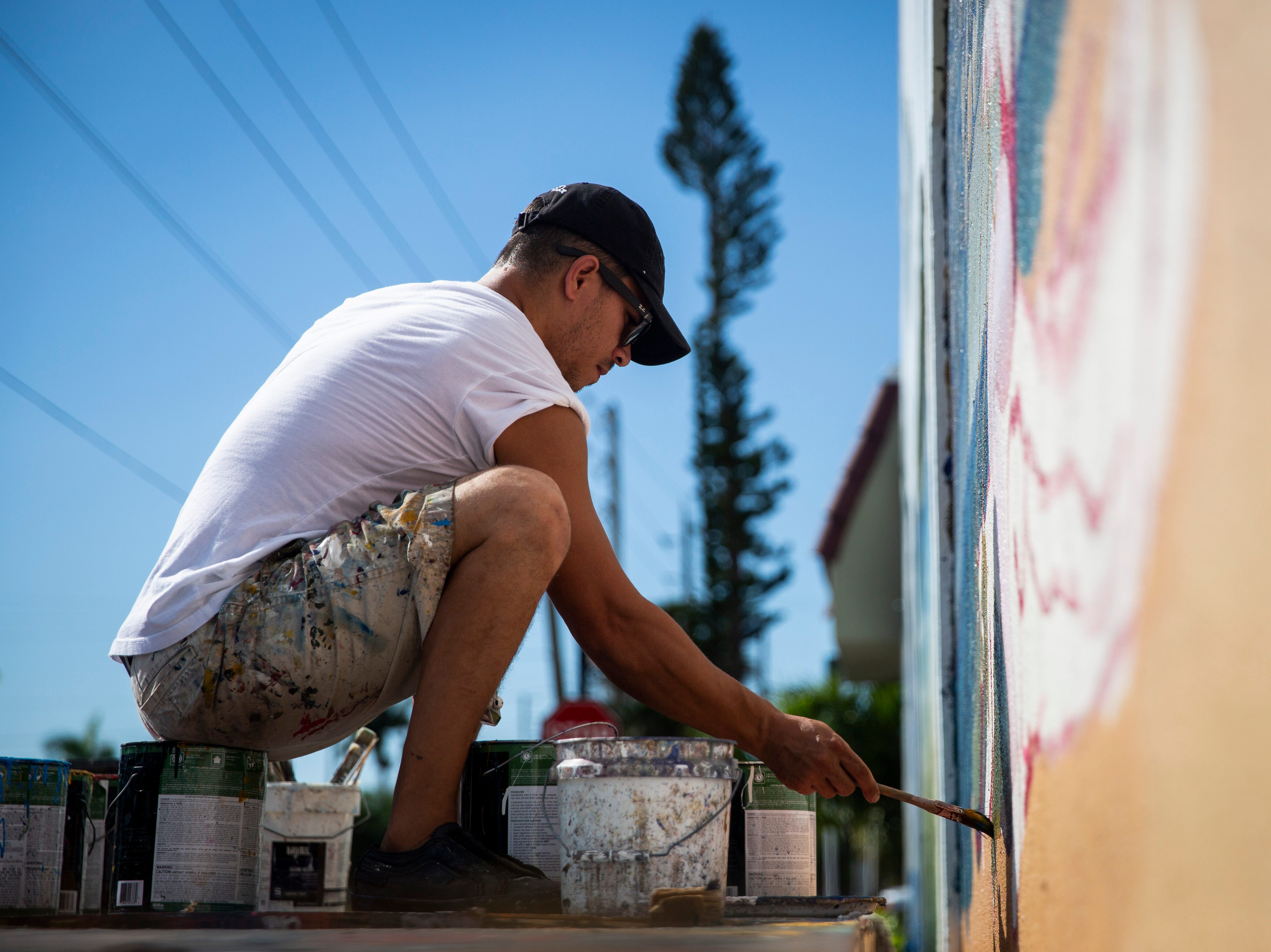 Naples artist Juan Diaz works on a mural on Friday, November 23, 2018, at the corner of U.S. 41 South and First Avenue South in Naples.