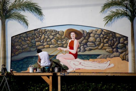 Naples artist Juan Diaz works on a mural on Friday, Nov. 23, 2018, at U.S. 41 South and First Avenue South in Naples. Each panel of the mural is based on a vintage postcard.