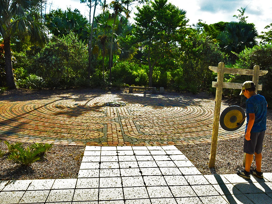 A large labyrinth is featured in the Scott Florida Garden located in Naples Botanical Garden. A young visitor to the garden rings a gong at the entrance to the labyrinth.