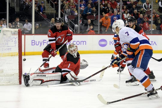 New York Islanders right wing Jordan Eberle (7) puts the puck into the net for a goal past New Jersey Devils goaltender Keith Kinkaid (1) as Devils defenseman Sami Vatanen (45) looks on during the first period of an NHL hockey game Friday, Nov. 23, 2018, in Newark, N.J.