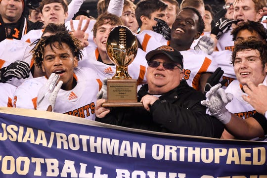 Hasbrouck Heights head coach Nick Delcalzo holds the trophy as his team poses for photographs after defeating Butler 41-7 in the North Group 1 final on Friday, Nov. 23, 2018, in East Rutherford.