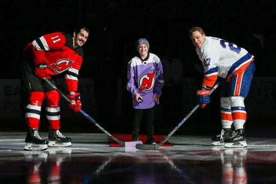 Nov 23, 2018; Newark, NJ, USA; New Jersey Devils center Brian Boyle (11) faces off against New York Islanders left wing Anders Lee (27) as Leukemia survivor Bennett Burgida, center, drops the ceremonial puck during the first period at Prudential Center.