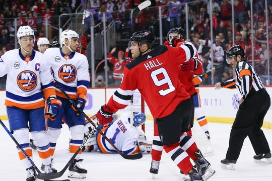 Nov 23, 2018; Newark, NJ, USA; New Jersey Devils left wing Taylor Hall (9) celebrates after scoring a goal against New York Islanders goaltender Thomas Greiss (1) during the second period at Prudential Center.