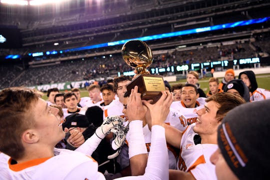 Hasbrouck Heights players hold the North Group 1 trophy after defeating Butler on Friday, Nov. 23, 2018, in East Rutherford.