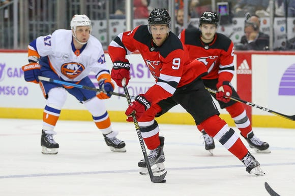 Nov 23, 2018; Newark, NJ, USA; New Jersey Devils left wing Taylor Hall (9) skates with the puck against New York Islanders right wing Leo Komarov (47) during the second period at Prudential Center.