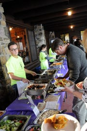 """West Milford High School Interact member, Spencer Englander, dishes out the tastes at the West Milford Education Foundation's annual """"A Taste of the Highlands"""" fundraising event in 2011."""