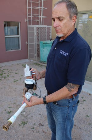 LCU Project Manager Fred Bourger shows what a new water meter looks like without the meter box and explains how the meters and sensors are connected to the ERTs, which are mounted to the lids of the meter boxes.