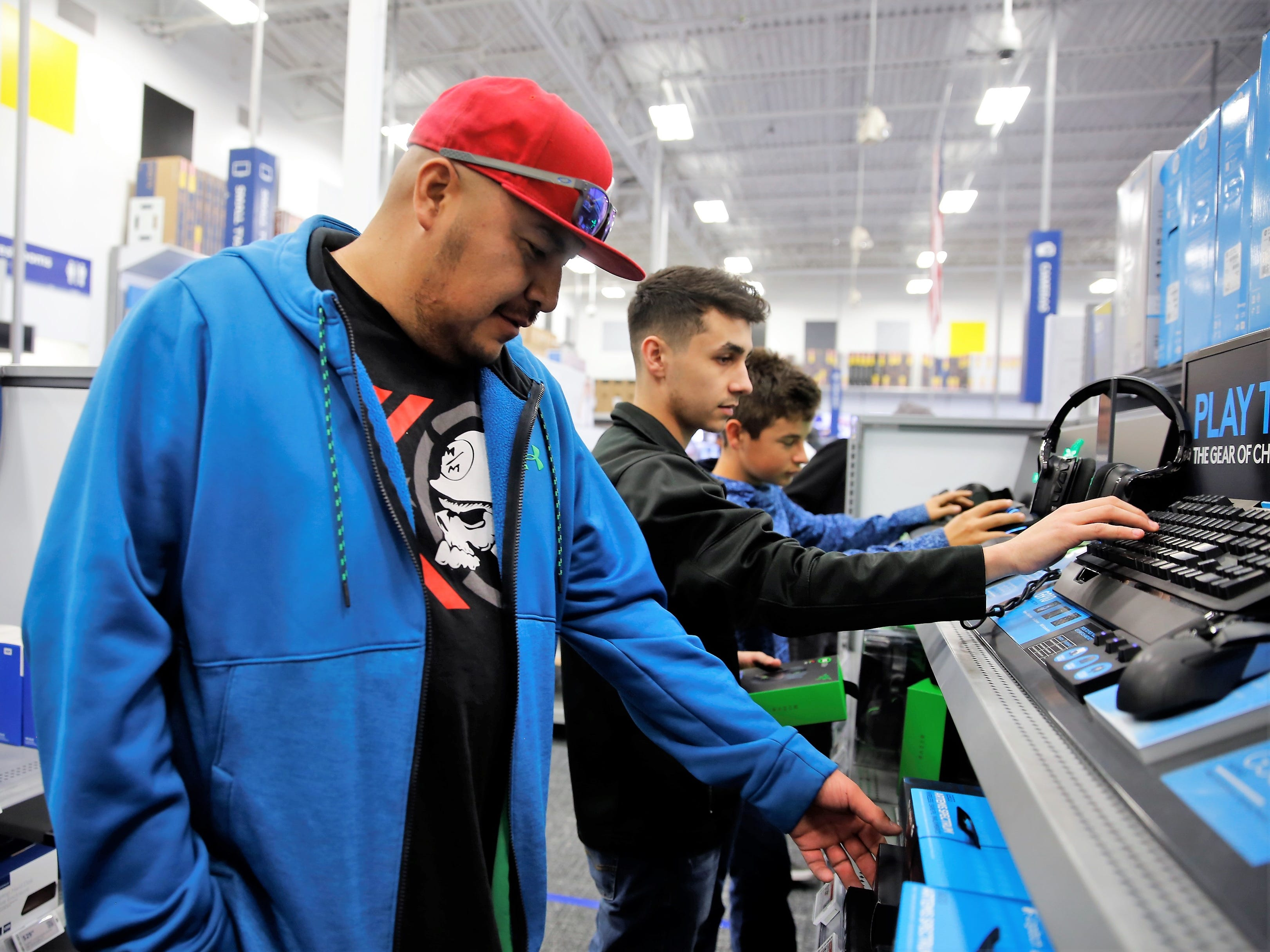 Terrence Benallie, left, Thomaslukes Florez-Mansi, center, and Estevan Florez-Mansi, right, look at personal computer accessories Friday afternoon at Best Buy in Farmington.