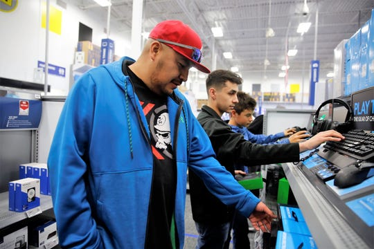 Terrence Benallie, left, Thomaslukes Florez-Mansi, center, and Estevan Florez-Mansi, right, look at personal computer accessories at Best Buy in Farmington in this file photo. Legions of shoppers are expected to descend on retails outlets in Farmington on Friday as Black Friday sales begin.