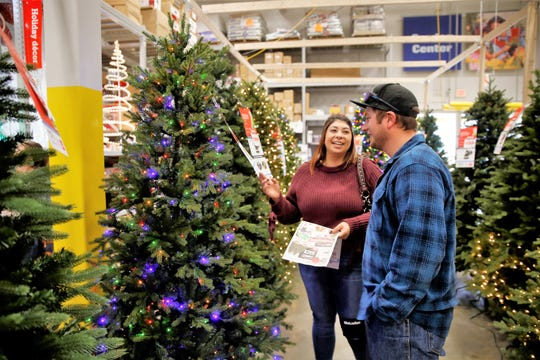 Katie Reynolds, left, and Keith Blackwell, right, shop for a Christmas tree Friday afternoon at the Lowe's home improvement store in Farmington.