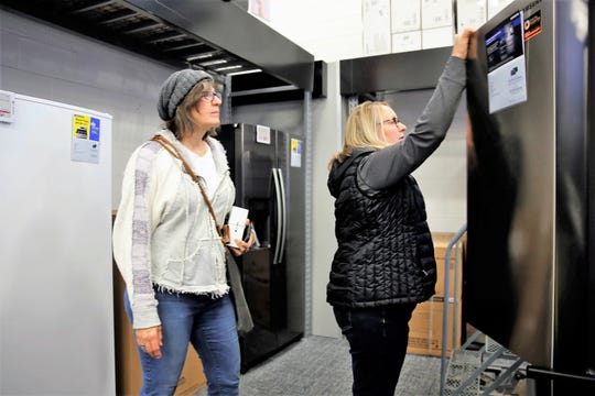T.J. Zark, left, and Lisa Stone, right, examine a refrigerator Friday afternoon at Best Buy in Farmington. Black Friday is projected to be the busiest shopping day of the holiday weekend.