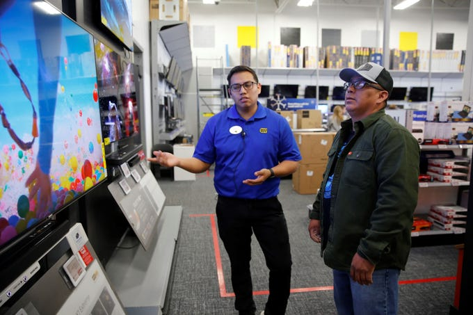Best Buy employee Sterling Begay, left, answers questions about televisions from Sylvester Begay Friday afternoon. Black Friday is projected to be the busiest shopping day of the holiday weekend.