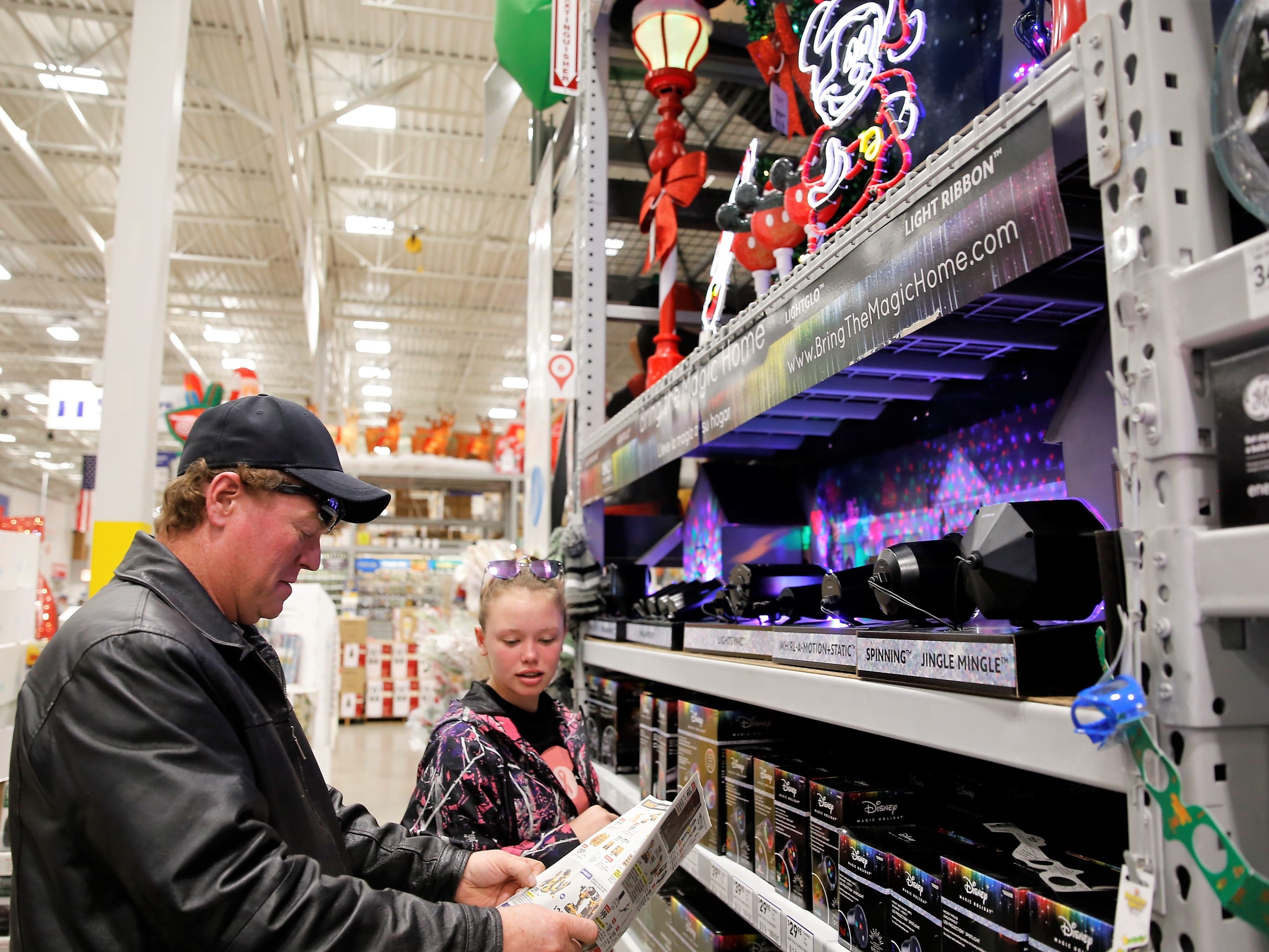 Ryen Christensen, left, and Hailey Christensen, right, look at a Lowe's home improvement store flyer as they shop for Christmas decorations Friday afternoon at Lowe's in Farmington.