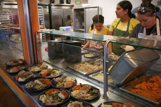 Volunteers serve food during a Thanksgiving meal at the Coachella Valley Rescue Mission in Indio, November 22, 2018