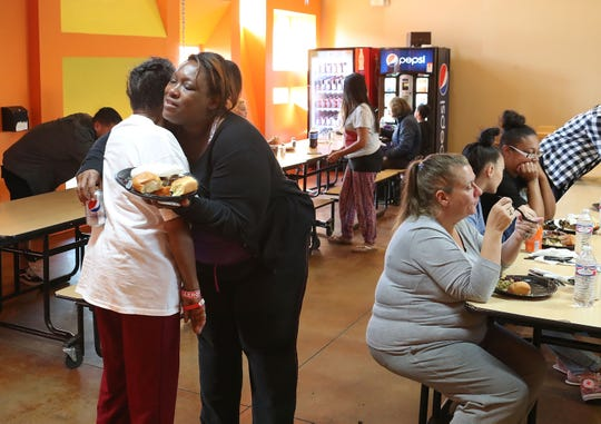 Two women greet each other during a Thanksgiving meal at the Coachella Valley Rescue Mission in Indio, November 22, 2018