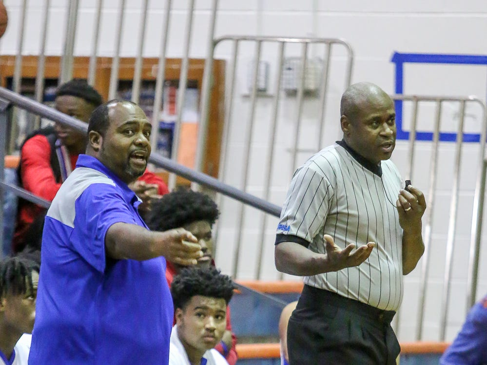 Washington head coach Dwayne Louis asks for clarification of a foul in the game against Navarre during the preseason basketball jamboree at Escambia High School on Tuesday, November 20, 2018. This is Posey's first year as the Raiders' head coach.