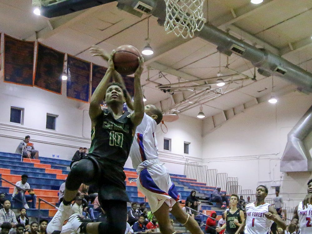 Pensacola Catholic's Jordon McCants (10) flies past a Pine Forest defender as he tries for a layup in the preseason basketball jamboree at Escambia High School on Tuesday, November 20, 2018.