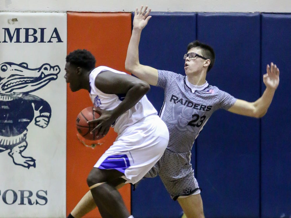 Navarre's Joseph Sczesny (23) tries to draw an offensive foul on Washington's David Gould (22) as Gould goes for a shot in the preseason basketball jamboree at Escambia High School on Tuesday, November 20, 2018.