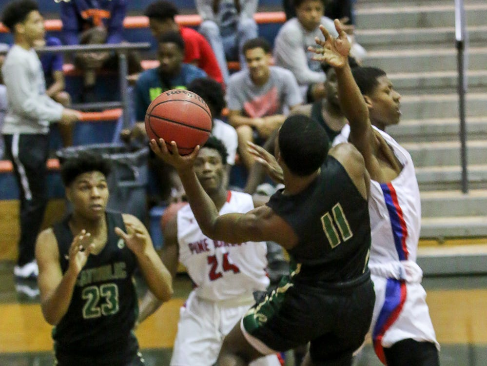 Pensacola Catholic's TJ McCants (11) tries for a leaping layup against Pine Forest in the preseason basketball jamboree at Escambia High School on Tuesday, November 20, 2018.