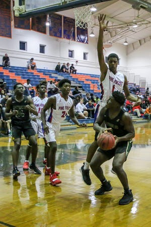 Pensacola Catholic's Jacobi Jackson (5) tries to find a shot around Pine Forest's Omarion Turner (1) in the preseason basketball jamboree at Escambia High School on Tuesday, November 20, 2018.