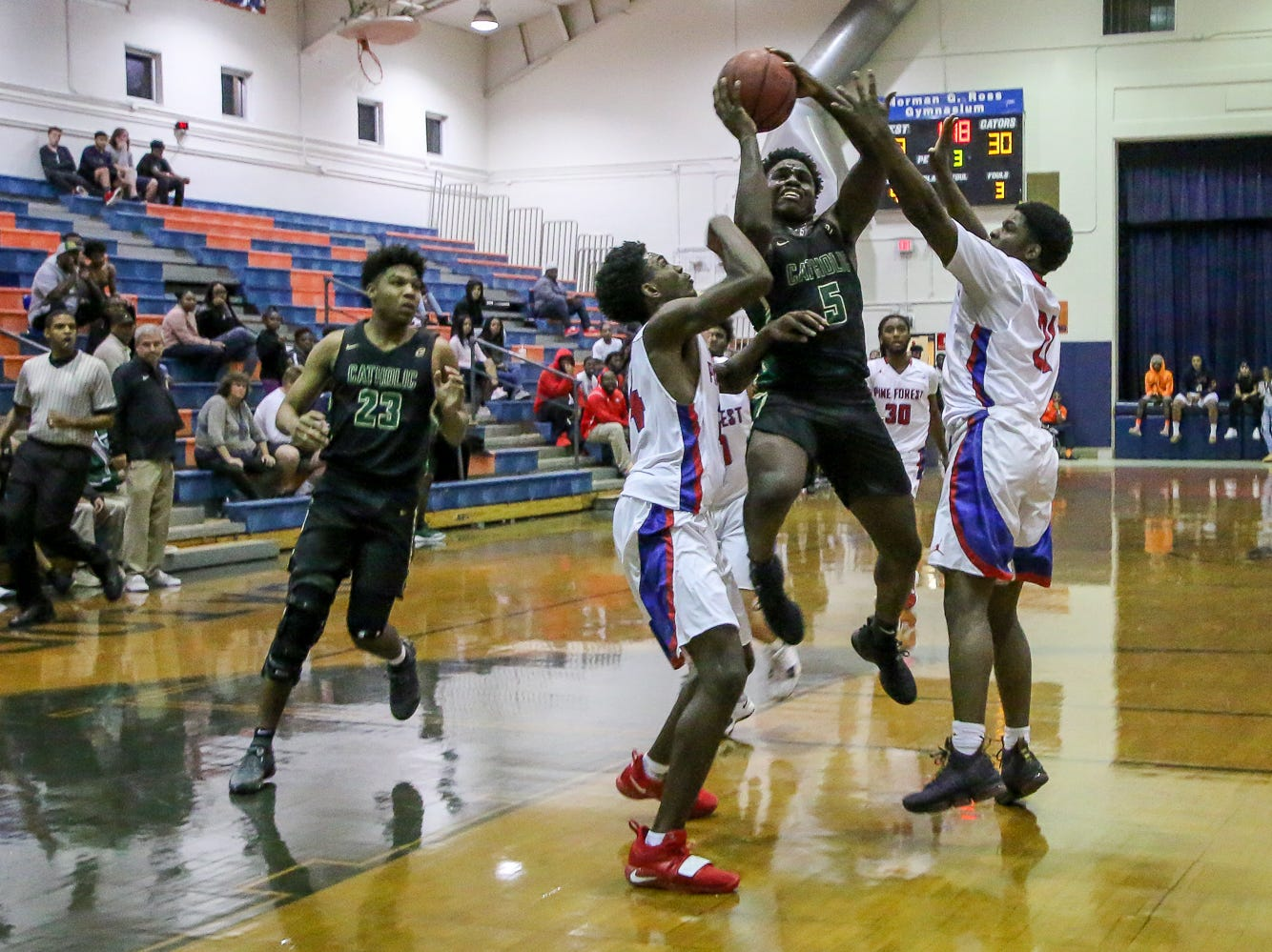 Pensacola Catholic's Jacobi Jackson (5) jumps between to Pine Forest defenders on his way toward the basket in the preseason basketball jamboree at Escambia High School on Tuesday, November 20, 2018.