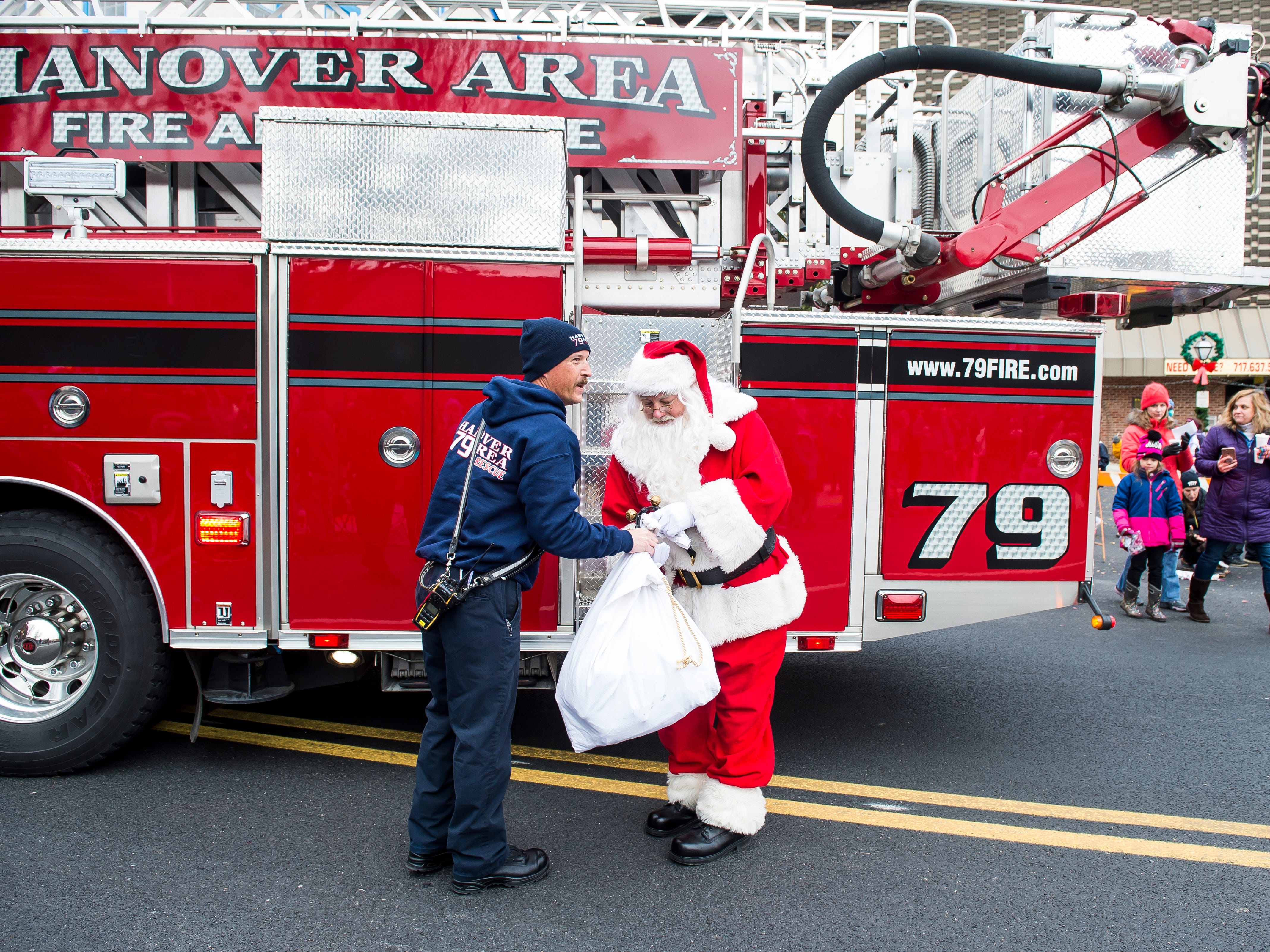 Santa gets some help with his bag from a member of Hanover Area Fire and Rescue during the annual Hanover Christmas parade on Friday, November, 23, 2018.