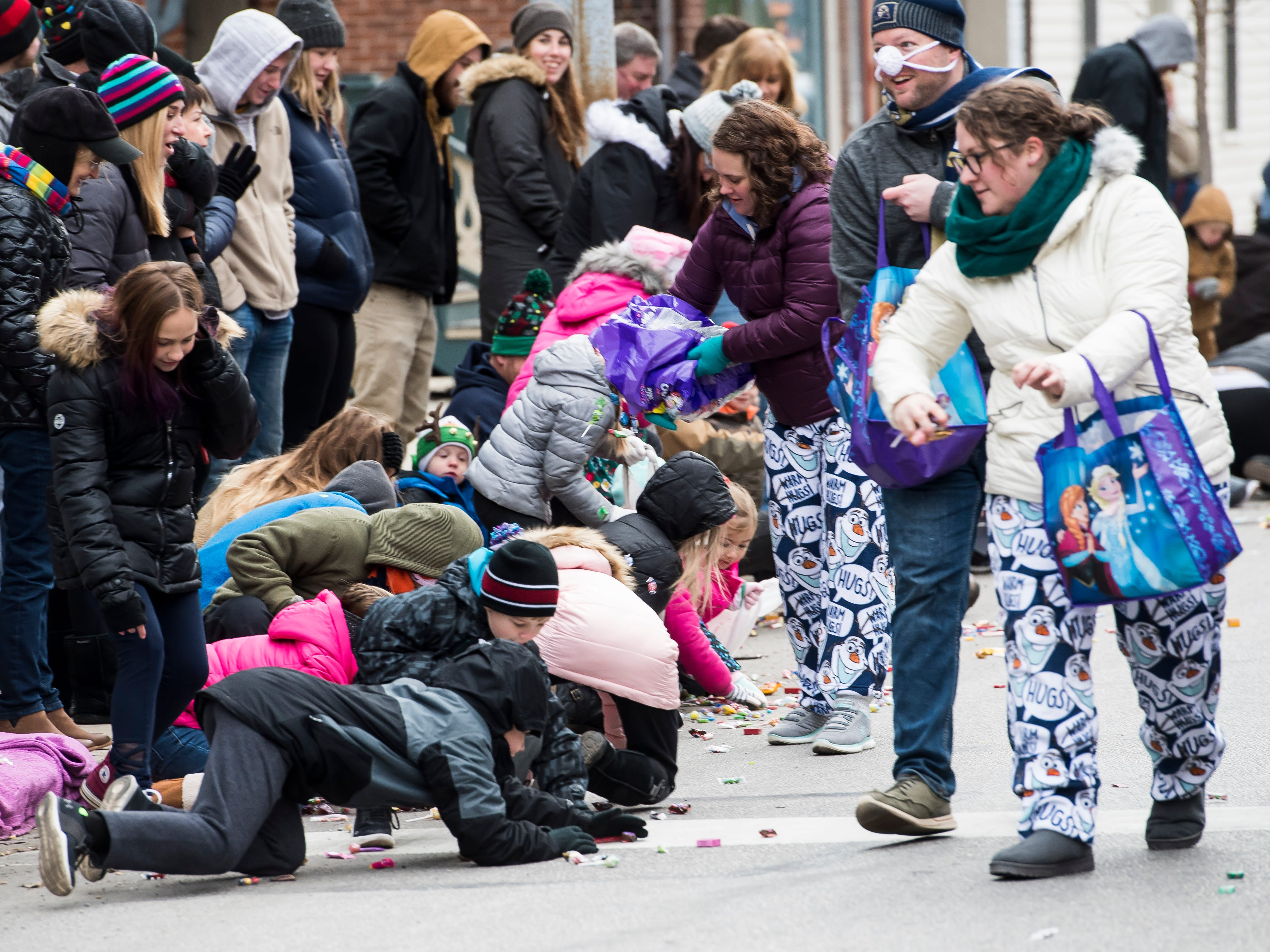 Children scramble to collect candy during the annual Hanover Christmas parade on Friday, November, 23, 2018.